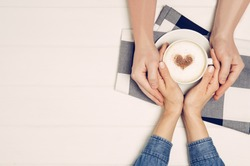 Couple in love holding hands with coffee on white wooden table. Photograph taken from above, top view with copy space
