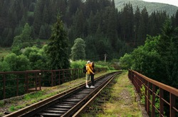 Couple in love hugging and kissing on a railway bridge in the mountains standing on the track. Tourists in love kissing against the backdrop of a beautiful landscape of cradles and forest in mountains