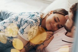 Couple in love is embracing on the bed. Man hugging and kissing his girlfriend