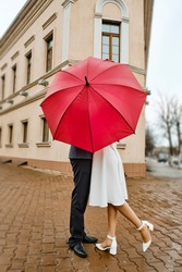 Couple in love kissing under red umbrella. Cute couple standing under umbrella. They closed with an umbrella from people