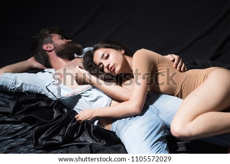 Couple in love lying in comfy bed. Bearded man embracing his brunette girlfriend. Muscular guy in denim shirt and jeans and sexy girl in beige body suit on black background.