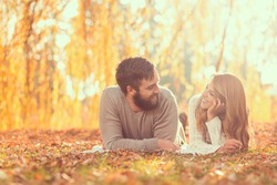 Couple in love lying on fallen autumn leaves under a tree in a park, enjoying a wonderful autumn day in nature. Focus on a man