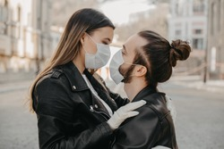 Couple in love, man and woman kissing each other in protective medical mask on face on asian street. Environmental pollution concept. Guy, girl against Chinese pandemic coronavirus, virus protection