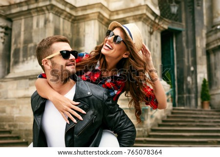 Couple In Love. Man Carrying Girl On His Back On Street. Smiling Male With Beautiful Young Woman Having Fun Spending Time Together. Relationships Concept. High Quality Image.