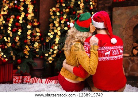 Couple in love, man male husband and woman female wife in santa elf hats and warm red sweaters hugging at home near Christmas tree anf fireplace before night of Christmas eve and Happy New Year 2019. #1238915749