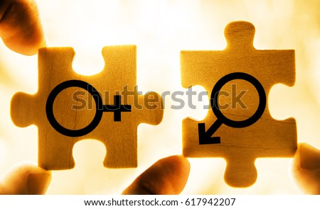 Couple In Love. Mars and Venus wooden symbols together. Hand holding wooden jigsaw puzzles. photo image, isolated on sunset sky background. Sword of Mars. Venus mirror
