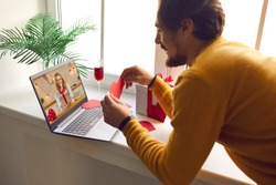 Couple in love miss each other in lockdown and look forward to meeting in person. Happy young man showing his girlfriend red heart card on romantic virtual date via video call on Saint Valentine's Day