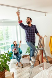 Couple in love moving in together, man standing on the ladder and setting up the apartment lighting while woman is drinking coffee and relaxing