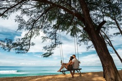 Couple in love on a swing by the sea. Couple in love on an island off the coast. Honeymoon. Couple by the sea. Man and woman travel to beautiful places. Honeymoon trip. Relax on the island. In love