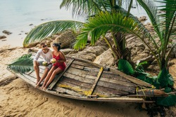 Couple in love on the seaside drinking coconut. Man and woman drink coconut. Honeymoon trip. Lovers on the beach. The man met a woman. Holiday romance. Sea tour. Couple travels. Couple on the island