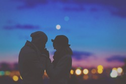 Couple in love on the street with defocused city lights.