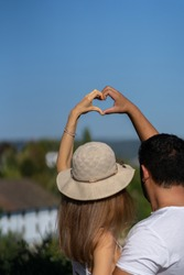 Couple in love raising arm up making heart together in the blue sky. Landscape in background.