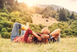 Couple in love rest on green hill in country side