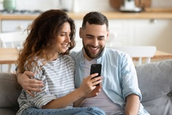 Couple in love resting on comfy couch having fun using smart phone apps, enjoy distant video call, wife showing interesting website to husband, choosing services goods on-line e-commerce usage concept