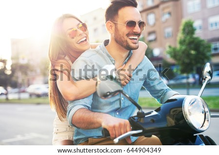 Couple in love riding a motorbike. Handsome guy and young sexy woman travel.