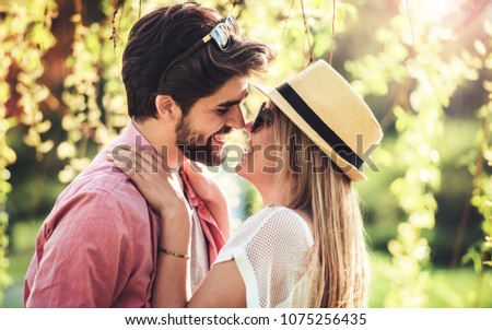 Couple in love. Romantic couple enjoying in moments of happiness in the city park. Love and tenderness, dating, romance. Lifestyle concept #1075256435