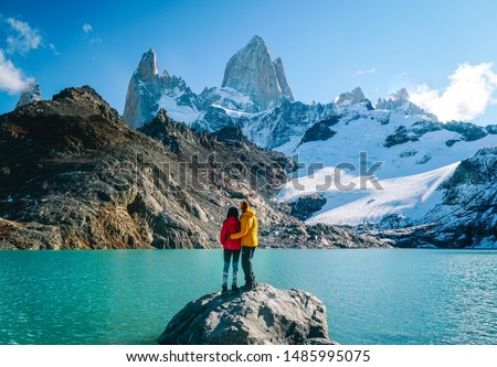 Couple in love & scenic view of snowcapped mountain tops of Mount Fitzroy, Patagonia trek. Blue sky, turquoise lake and scenic rock landscape. Shot in Argentina. Nature, travel, adventure, hiking.