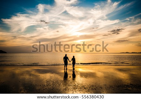 Couple in love see sunset at the beach