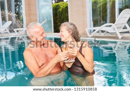 Couple in love seniors drinking champagne together in the pool at the Wellness Hotel