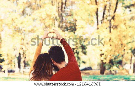 Couple in love shows heart sign with fingers. Dating and autumn love concept. Girl and bearded guy or happy lovers on a date. Man and woman turned backwards on autumn trees background
