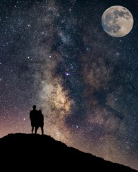 Couple in love silhouette and the Milky way, love and valentines concept, long exposure astronomical photograph full moon and milkyway, apic shot from israel desert.