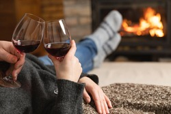 Couple in love sitting in a cozy room with fire place on a sofa with glass of wine. Family and love concept.