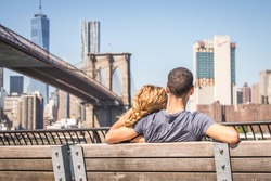 Couple in love sitting on a bench and staring at Brooklyn Bridge and Manhattan skyline - Romantic date