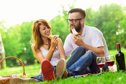 Couple in love sitting on a picnic plaid in a park, eating sandwiches, drinking wine and enjoying the day
