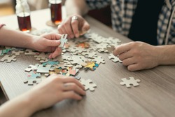 Couple in love sitting on the floor next to a table, solving a jigsaw puzzle problem and enjoying their leisure time activities.