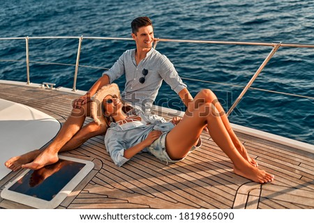 Couple in love sitting on yacht deck while sailing in the sea. Handsome man and beautiful woman having romantic date. Luxury travel concept.