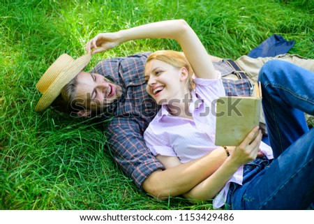 Couple in love spend leisure reading book. Man and girl lay on grass relaxing. Romantic couple family enjoy leisure with poetry or literature grass background. Couple soulmates at romantic date.
