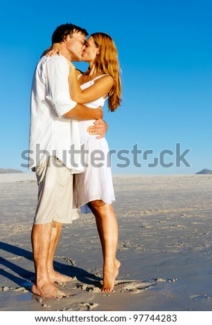 Couple in love stand on the beach in summer and share a kiss at sunset alone and on honeymoon.