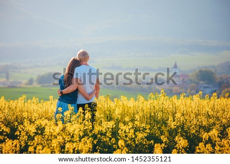 Couple in love standing in yellow spring nature. Romantic photo, man and woman, white edit space #1452355121