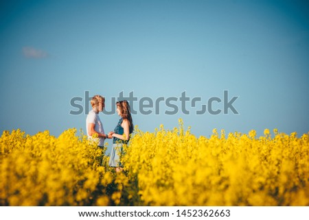 Couple in love standing in yellow spring nature. Romantic photo, man and woman, white edit space #1452362663