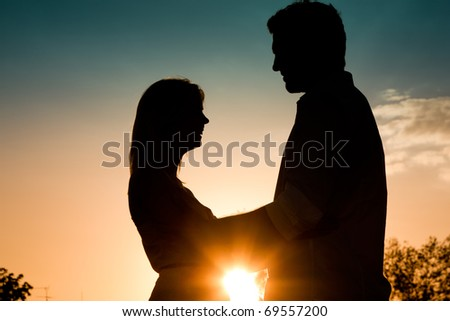 Couple in love touching each other backlit in a sunset in summer