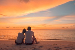 Couple in love watching sunset together on beach travel summer holidays. People silhouette from behind sitting enjoying view sunset sea on tropical destination vacation. Romantic couple on the beach