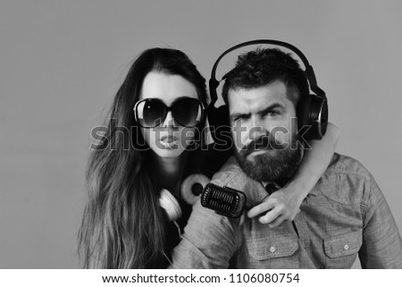 Couple in love wears headphones and holds microphone. Man with beard and girl hug on grey background. Pleasure, music and creative lifestyle concept. Music fans with concentrated faces wear sunglasses #1106080754