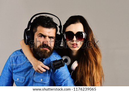 Couple in love wears headphones and holds microphone. Man with beard and girl hug on grey background. Pleasure, music and creative lifestyle concept. Music fans with concentrated faces wear sunglasses #1176239065