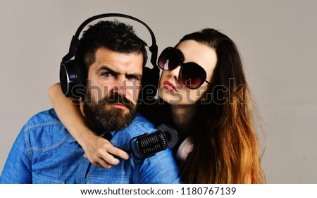 Couple in love wears headphones and holds microphone. Man with beard and girl hug on grey background. Pleasure, music and creative lifestyle concept. Music fans with concentrated faces wear sunglasses #1180767139