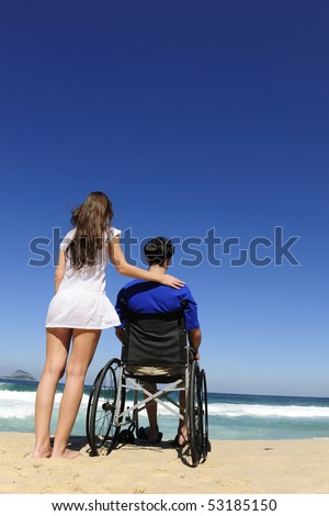 couple in love:  woman and husband in wheelchair on the beach
