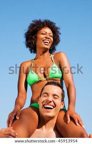 Couple in love - Woman of Brazilian origin in bikini sitting on her man's shoulders under blue sky - summer and fun