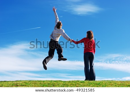 Couple in meadow. Man jump to the sky. Conceptual design. - stock photo