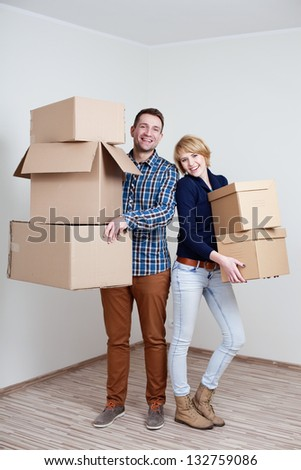 Couple in new home holding boxes