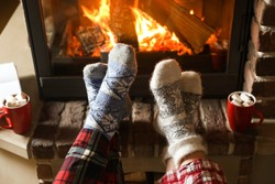 Couple in pajamas resting near fireplace indoors, closeup. Winter vacation