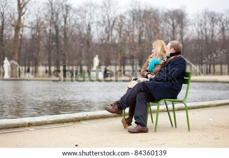 Couple in Paris, sitting in the Tuilleries park - stock photo