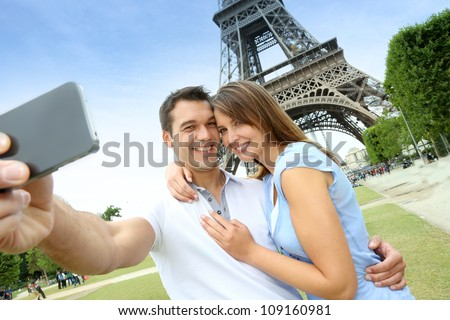 Couple in Paris taking pictures in front of Eiffel Tower
