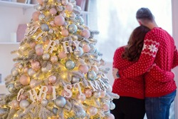 Couple in red knit sweaters stand near Christmas tree and looking to window. Man and woman in Christmas interior room