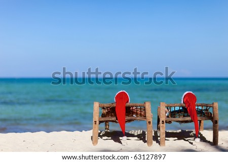 Couple in red Santa hats at tropical beach relaxing on sun beds