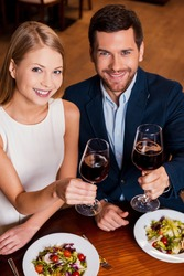 Couple in restaurant. Top view of beautiful young loving couple toasting with red wine while sitting at the restaurant together