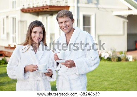 Couple in robes with cups outdoors